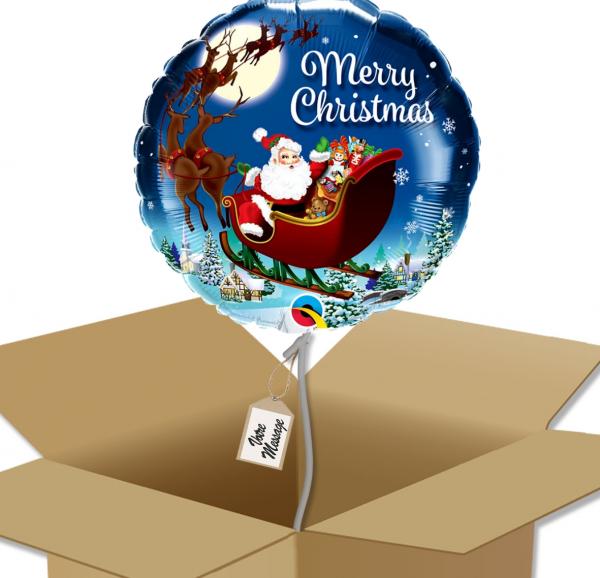 """Ballon rond écriture """"Merry Christmas"""" avec dessin traineau et village du père noël dans sa boîte."""